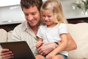 Father and worried daughter using a digital tablet on the sofa